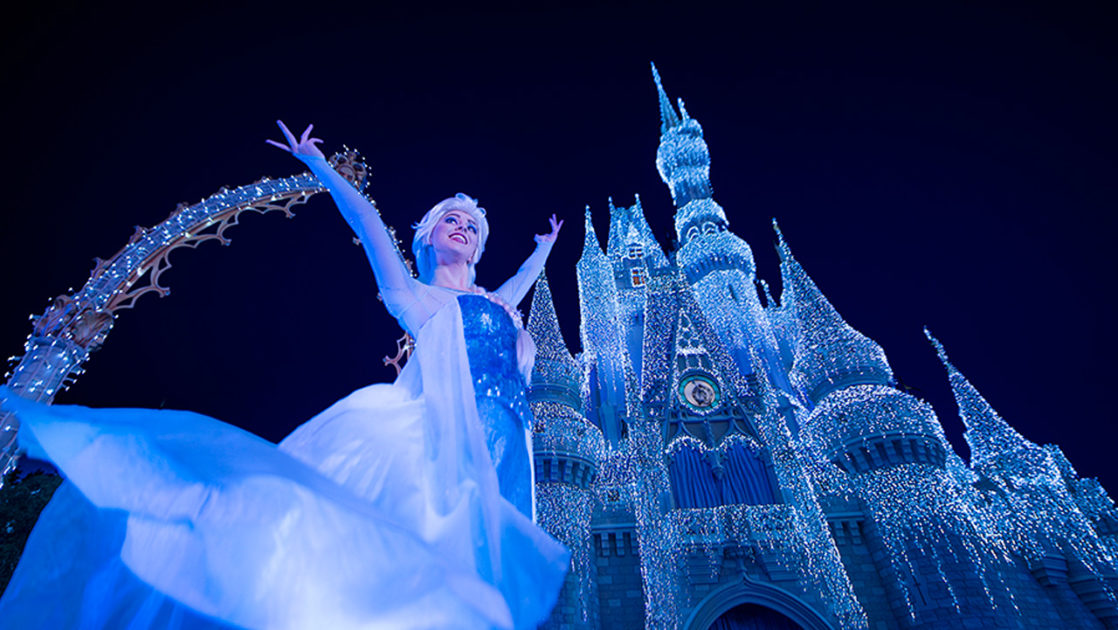 Elsa appearing in front of the Sleeping Beauty Castle for Mickey's Christmas Party.
