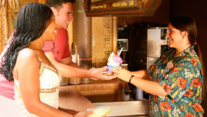 A Cast Member handing two Disney park guests a Dole Whip treat