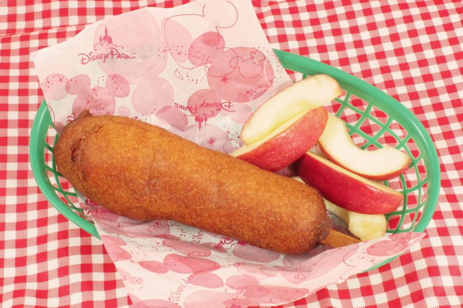 Close up of corn dog in a basket with apple slices.