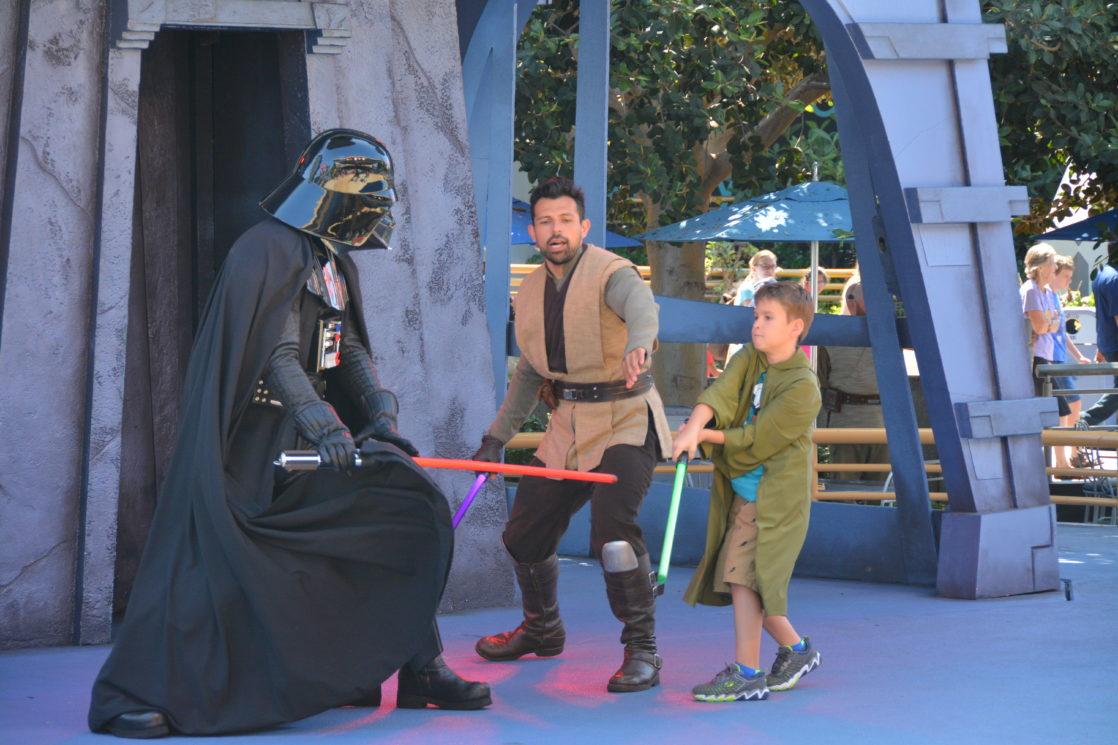 Child battling Darth Vader with lightsaber