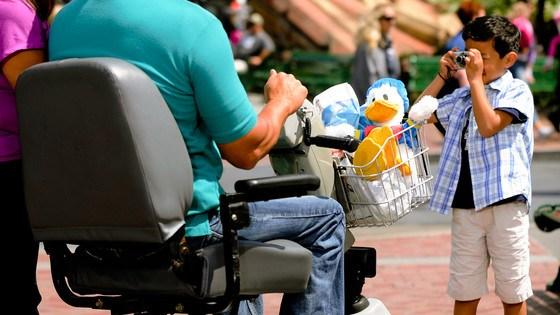 Man in wheelchair gets picture taken by child