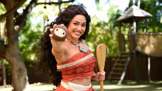 Moana holding out a coconut and smiling