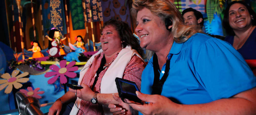 Guests with Disabilities: Disneyland guests smiling as they watch a show