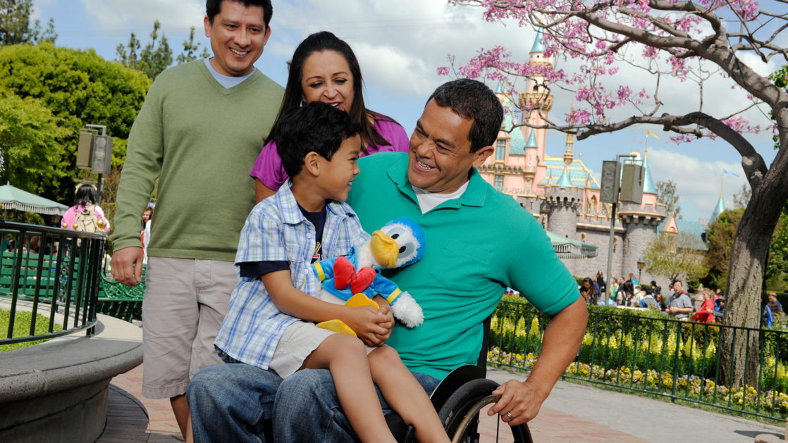 Family with child in lap of a man in a wheelchair.