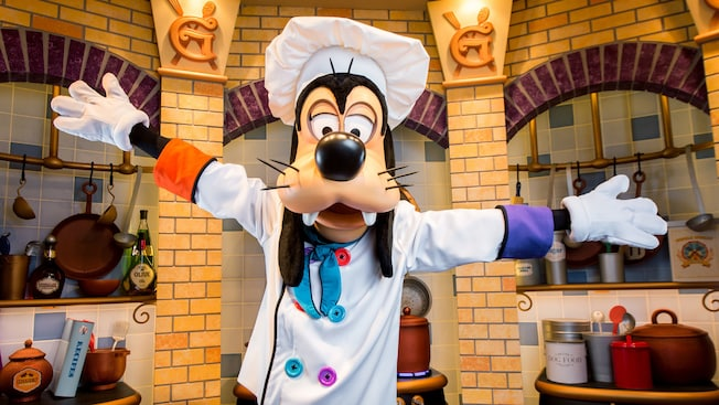 Goofy throws his arms out dressed in a chef costume