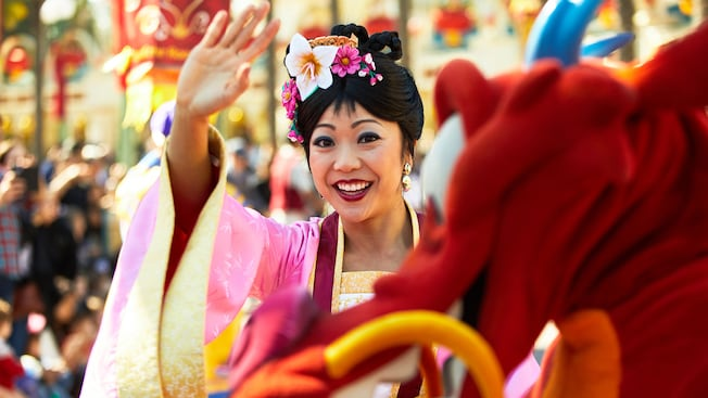 Mulan waving from a parade float