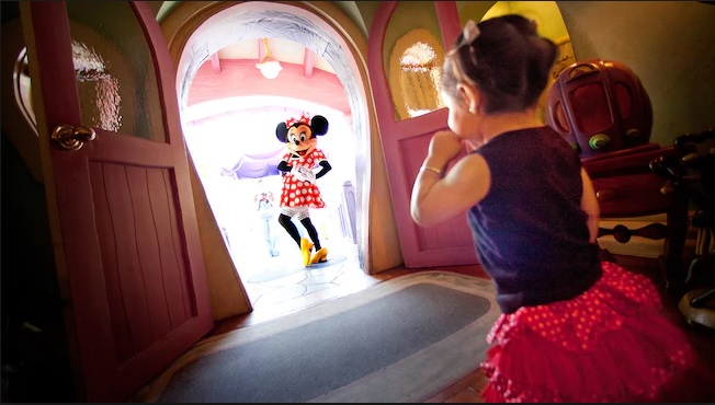 innie standing in the doorway of her house in Toontown while little girl looks in