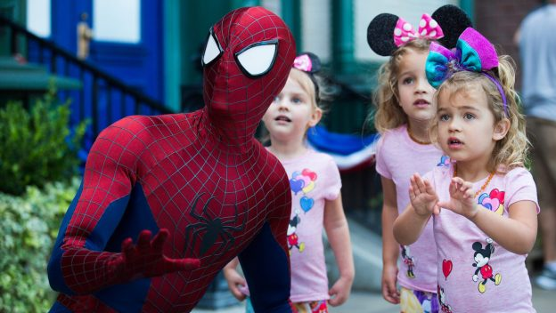 Spiderman kneeling down by three small children during a meet and greet