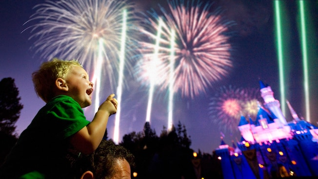 Child watching fireworks over Sleeping Beauty's Castle