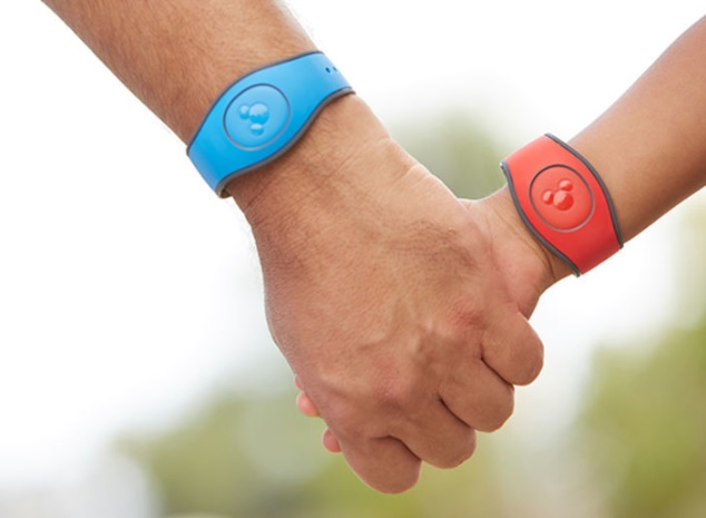 Son and child holding hands with Magic Bands on wrists