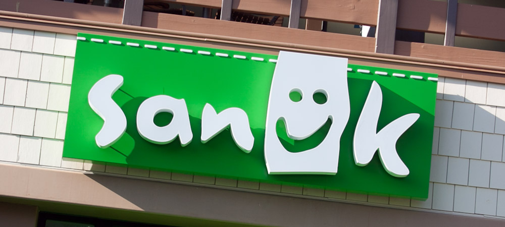 The green Sanuk logo