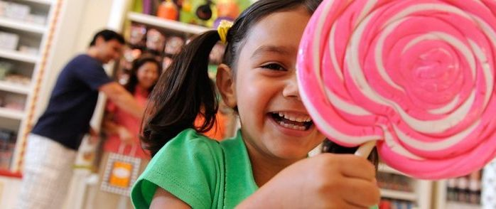 Little girl smiles while holding pink and white lollipop