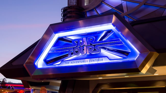 The Star Tours sign lit up during the evening