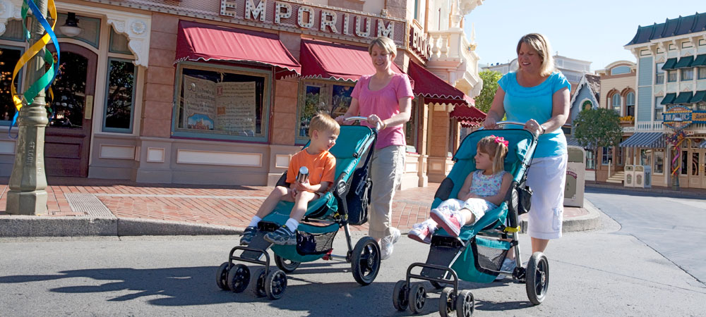 Two moms pushing strollers with their children on Main Street