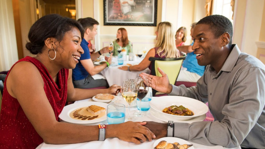 Man and woman smiling while eating a fancy dinner