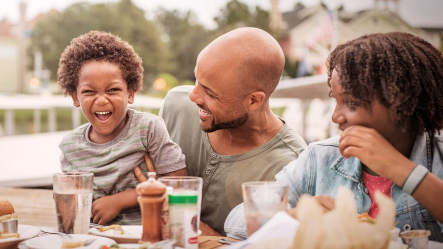 Mom and dad smiling at little boy eating