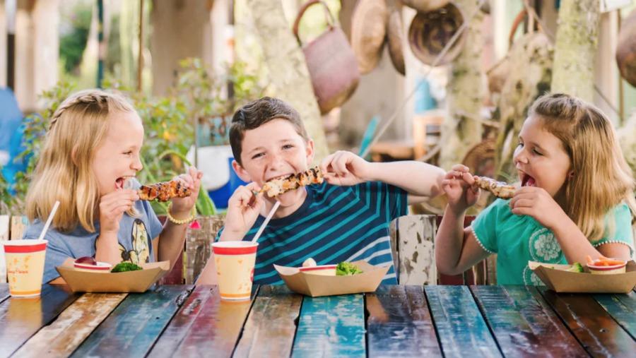 Three kids eating food at Walt Disney World