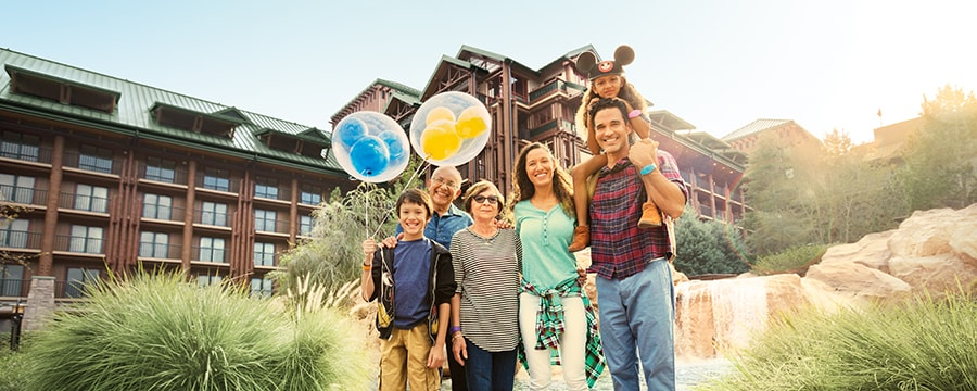 Family standing in front of a resort holding a Mickey balloon