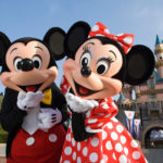 Mickey and Minnie blowing kisses in front of Sleeping Beauty's Castle