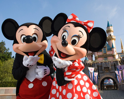 Mickey and Minnie Mouse blowing kisses in front of the castle