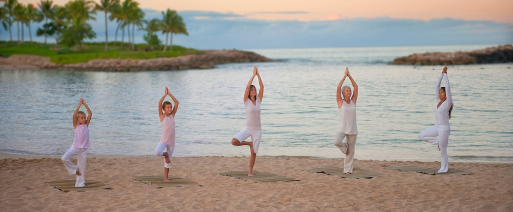 Guests doing yoga on the beach