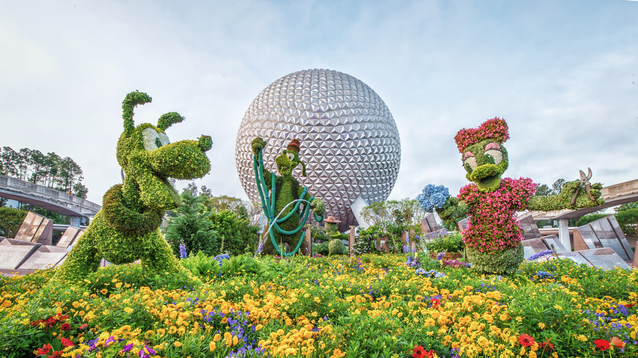 Epcot with garden in front and sculptures of Disney characters out of plants