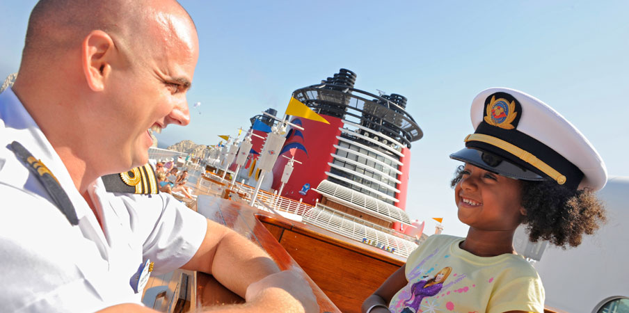 Captain talking with little girl with captain's hat on