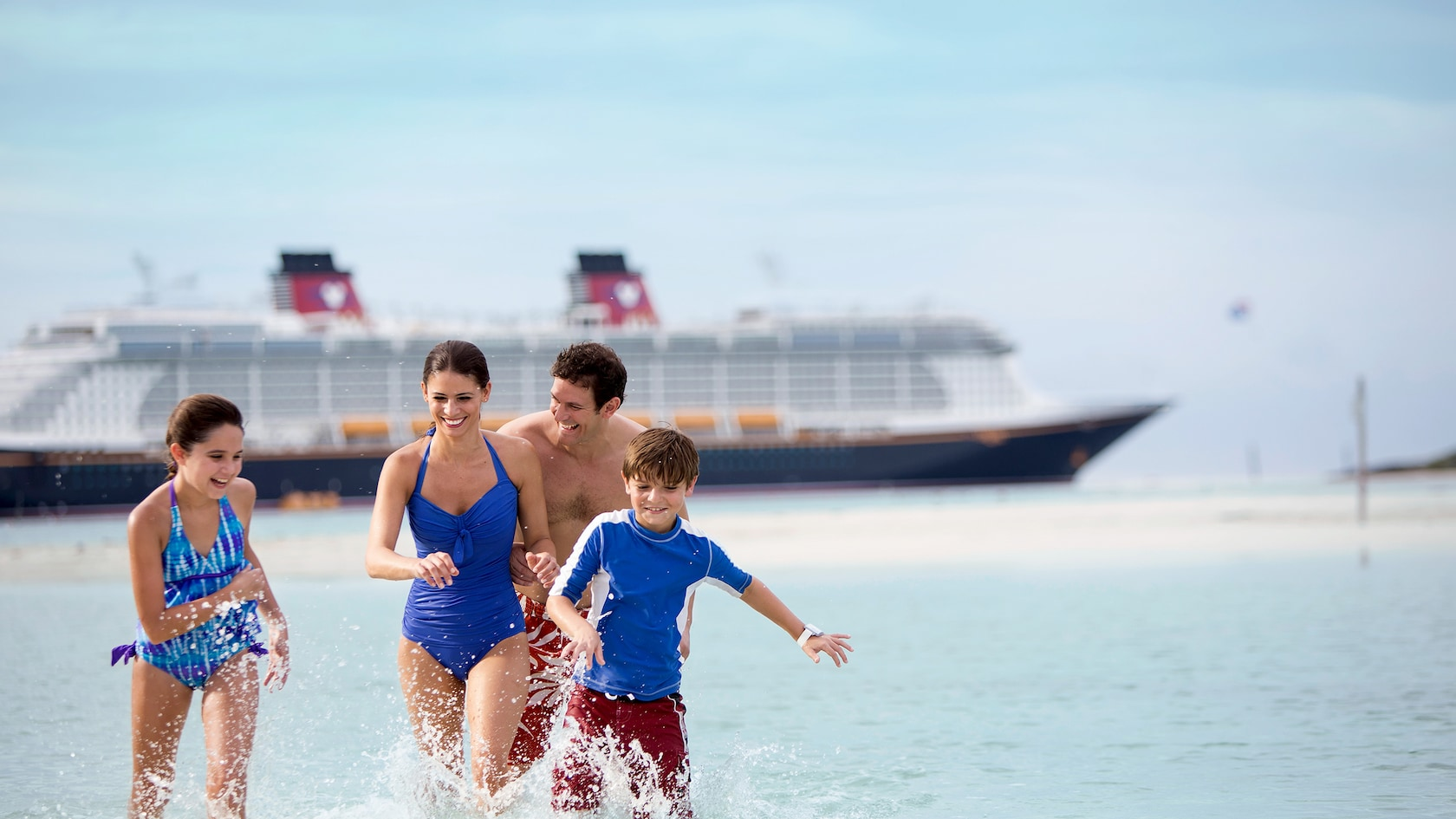 Family splashing in the ocean with Disney Cruise boat in the background